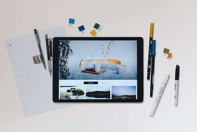 An iPad with a collection of pens, pencils, and paper.
