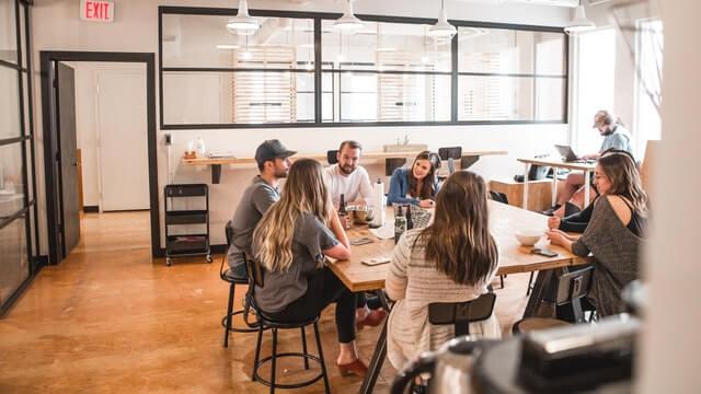 Talking people sitting beside a table.