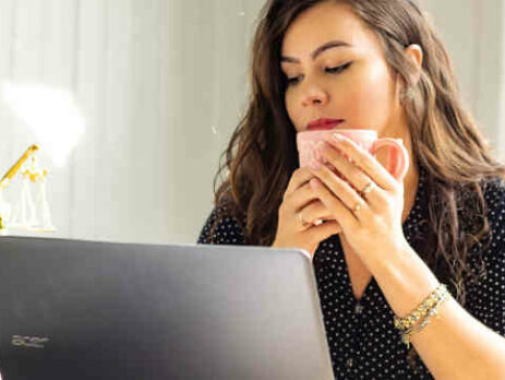 A woman drinking coffee and looking at a computer.