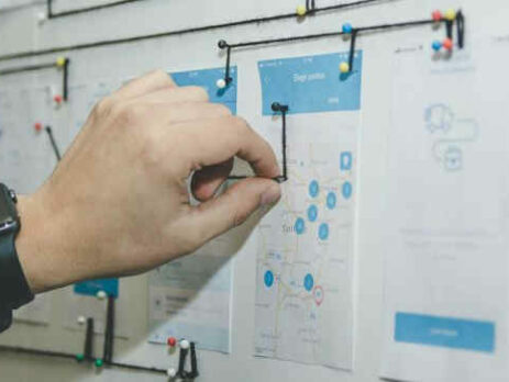 A person works with blue and white paper on a bulletin board.