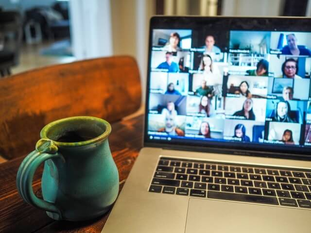 Video call on a computer screen with a cup of coffee.
