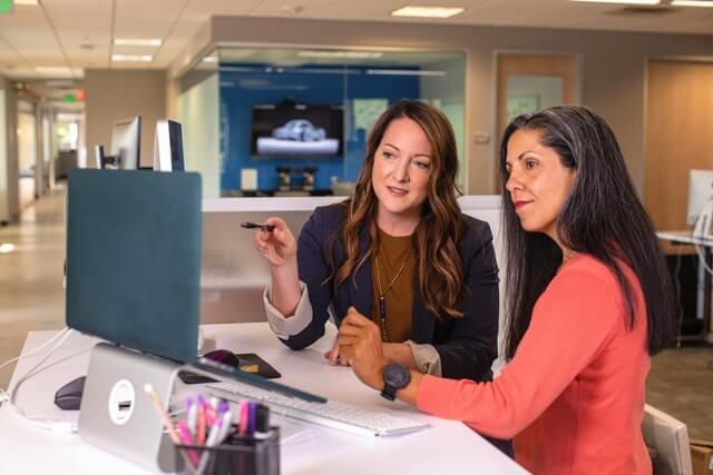 Two businesswomen talking near a computer.