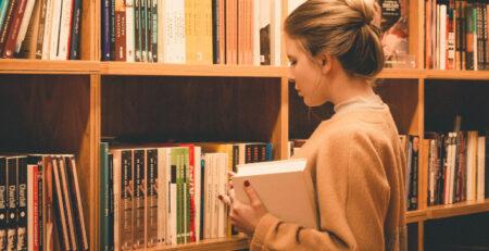 A woman chooses a book from a bookshelf.