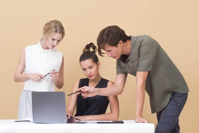 A man and two women talking near a laptop.