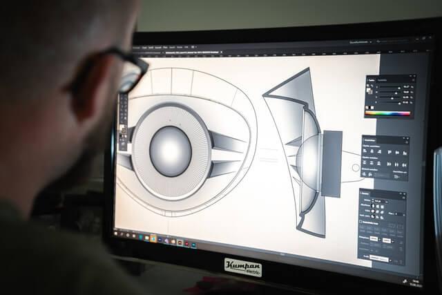 A man looking at a black flatscreen computer monitor.
