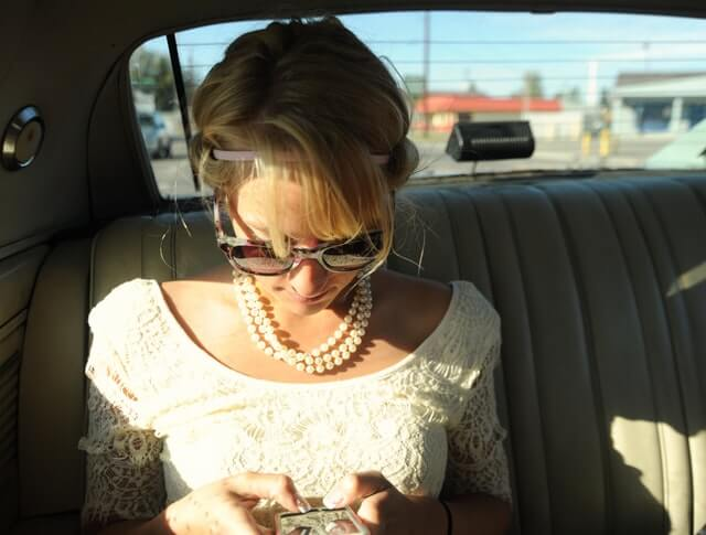 A woman in a white shirt types on her phone in the back seat of a car.