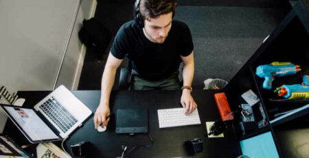 A man sitting at a desktop computer working.