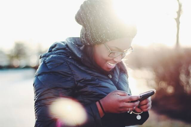 A smiling young woman in a black coat and green hat uses a smartphone.