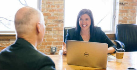 A woman with a laptop talks with a man at a brown table.