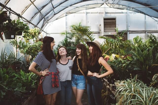 Four women laugh inside of a greenhouse.