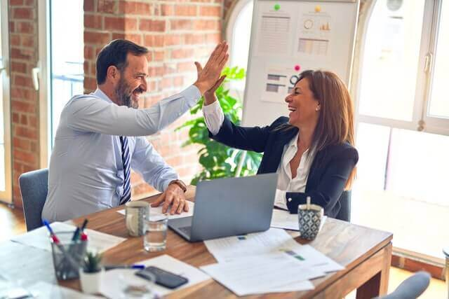 A man and a woman high five each other during a work meeting.