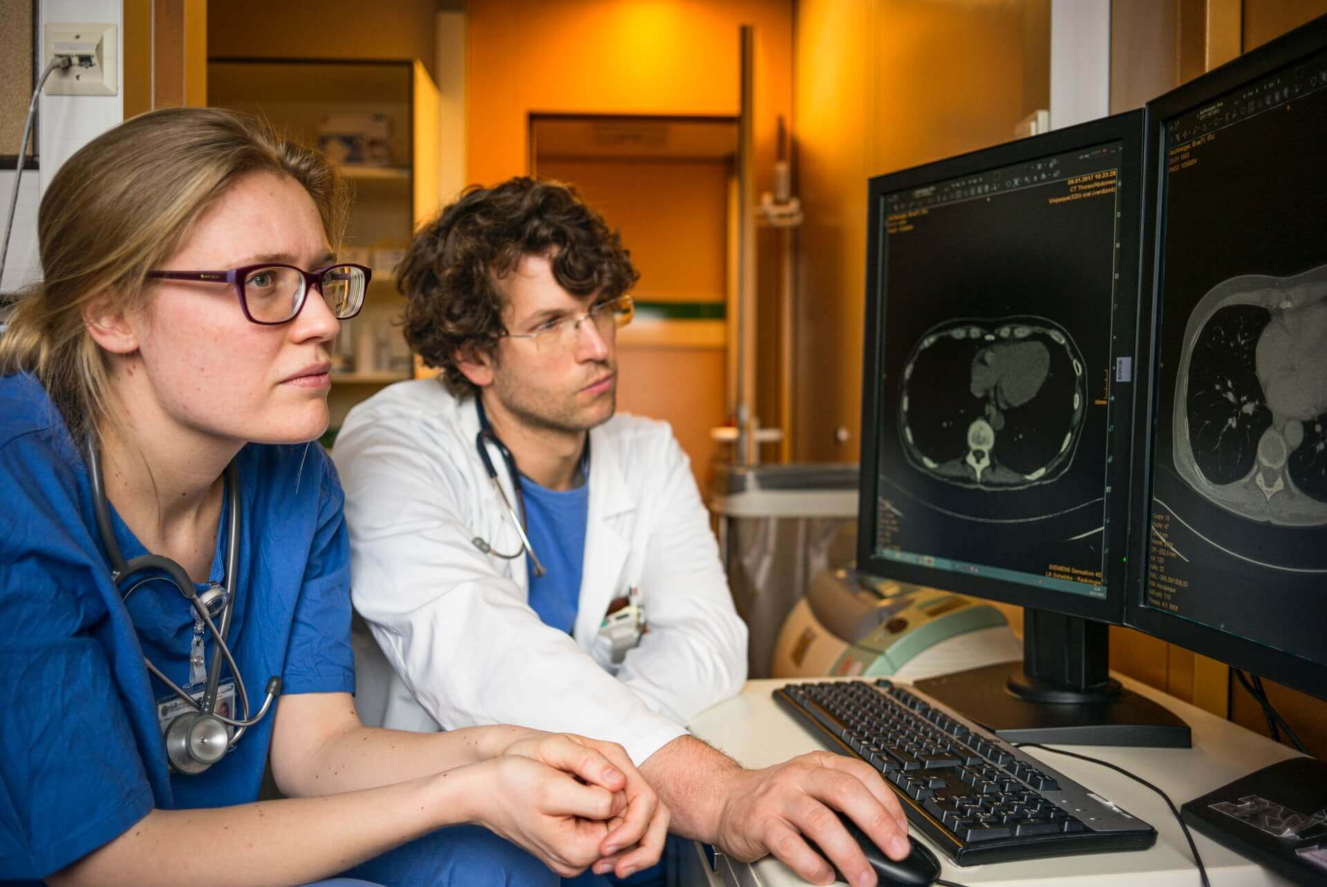 Two doctors look at MRI results on a computer screen.