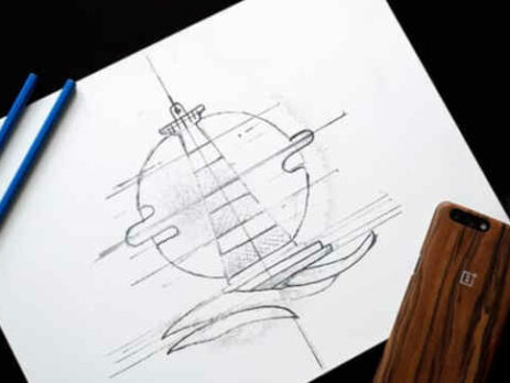 Two blue colored pencils next to an iPhone and a drawing of a lighthouse.