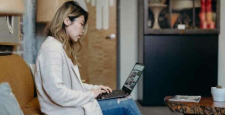 A woman wearing a white sweater works on a laptop at home.