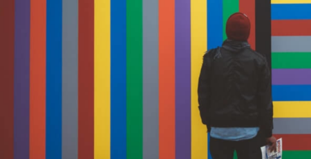 A man in a red beanie looks up at a colorful wall.
