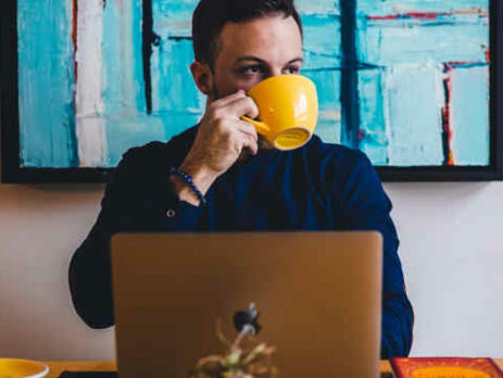 A man drinks coffee from a yellow mug while working on a laptop.