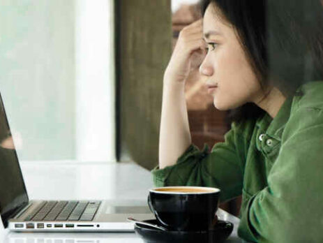 A woman wearing a green jacket looks at a laptop in a cafe.