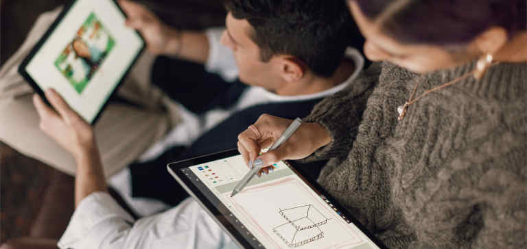 A woman draws on a tablet.