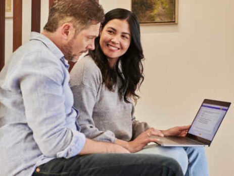 A man and woman work together on a laptop.