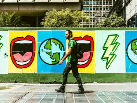A man wearing a green shirt walks in front of a mural.