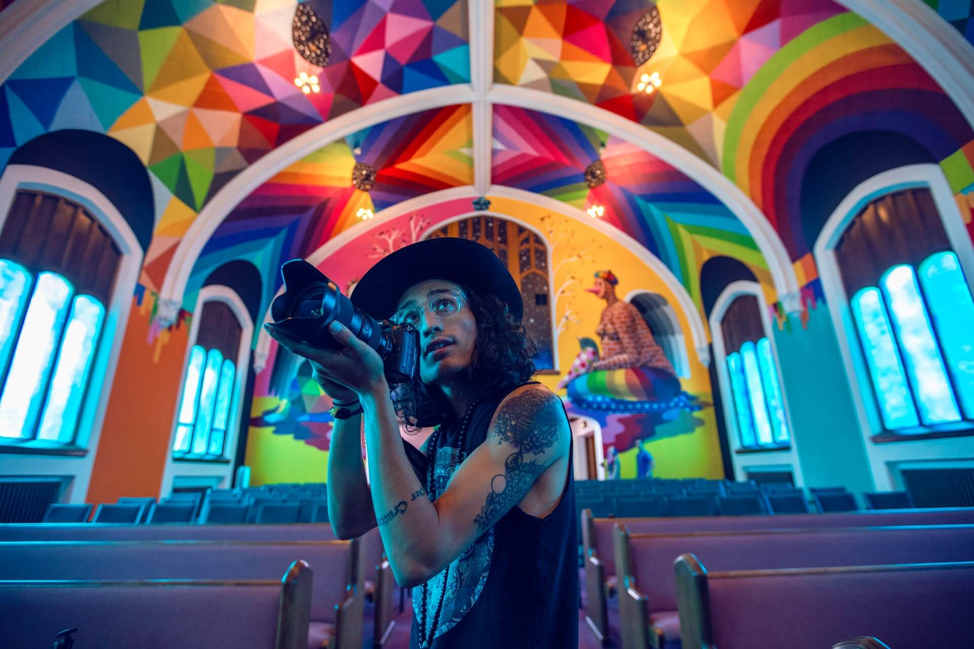 A man with a camera takes pictures underneath a colorful ceiling.