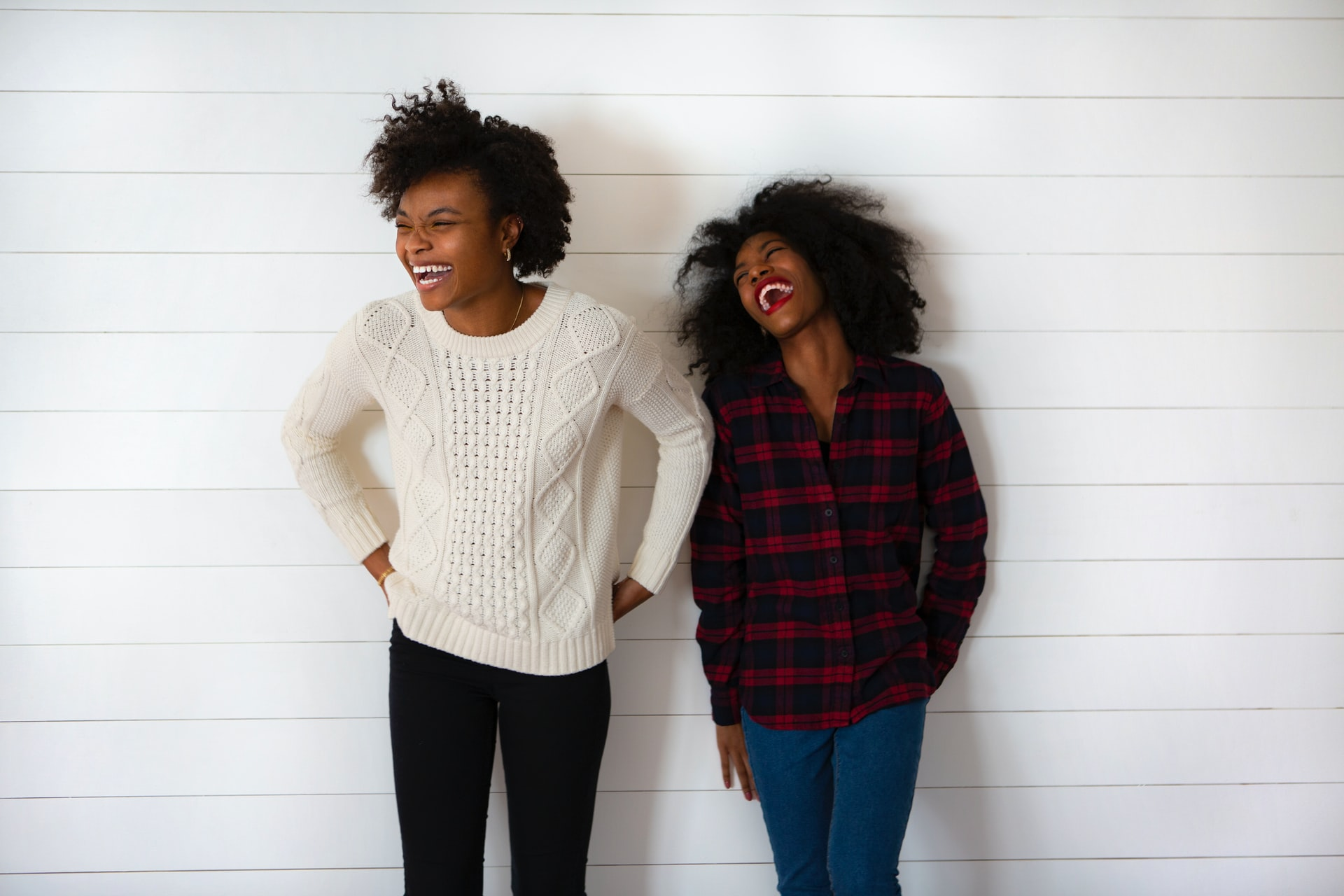 Two women stand against a wall and laugh.