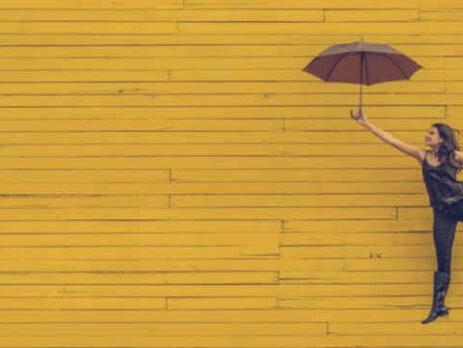 A woman holds a black umbrella near a yellow wall.