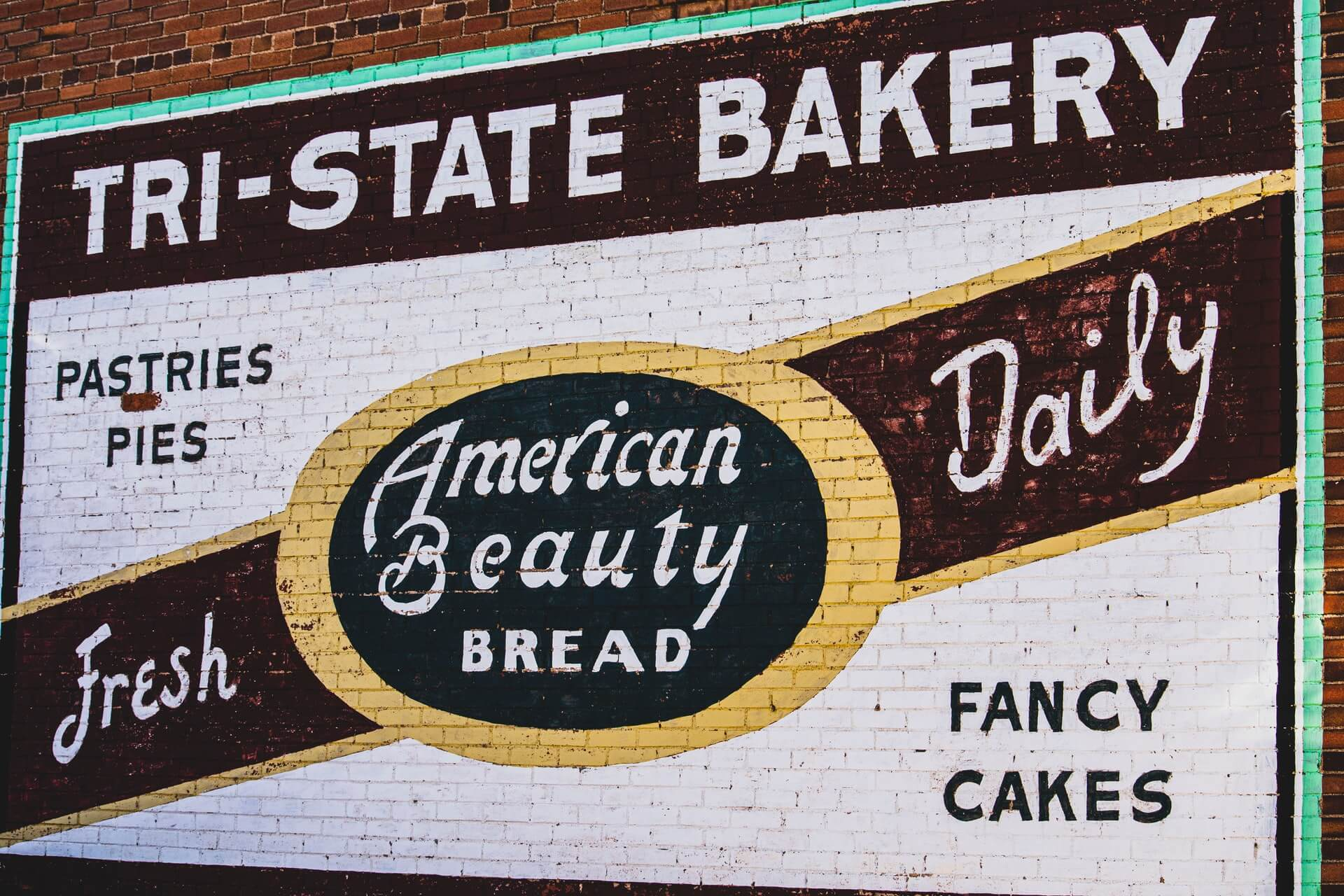 A painted advertisement for a bakery on a brick wall.