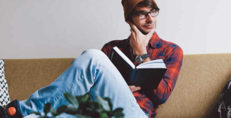 A man in an orange hat sits reading a book.