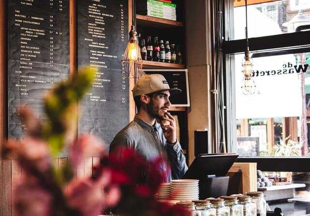 A man wears a hat behind the counter of a small restaurant.