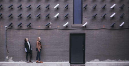 Two women look up at many black and white security cameras.