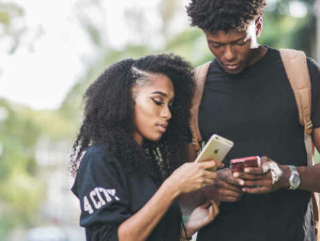 A man and woman compare smartphones with one another.