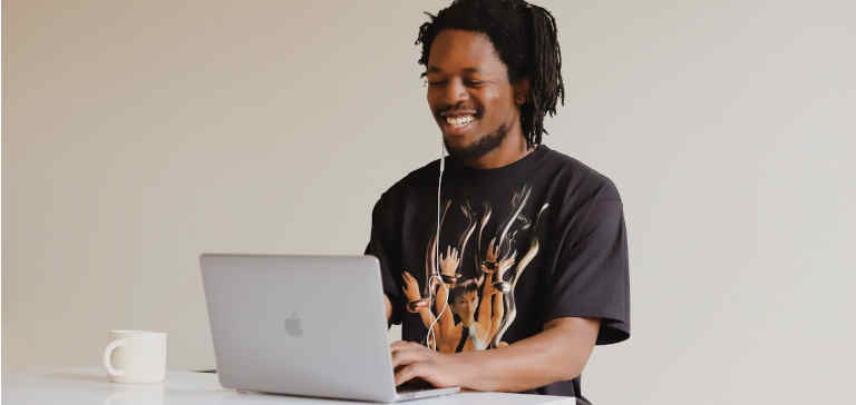 A man in a black t-shirt works on his laptop with a cup of coffee.