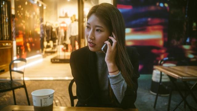 A woman talks on a cell phone inside a cafe.