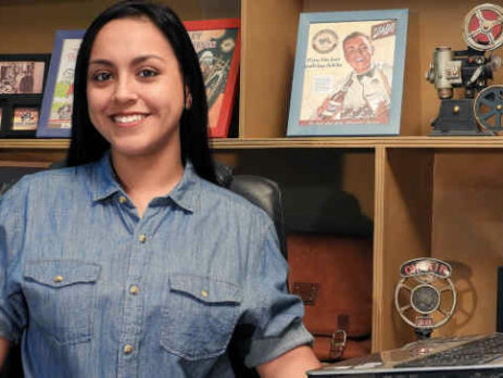 A woman in a blue shirt sits near a computer and some framed photos.