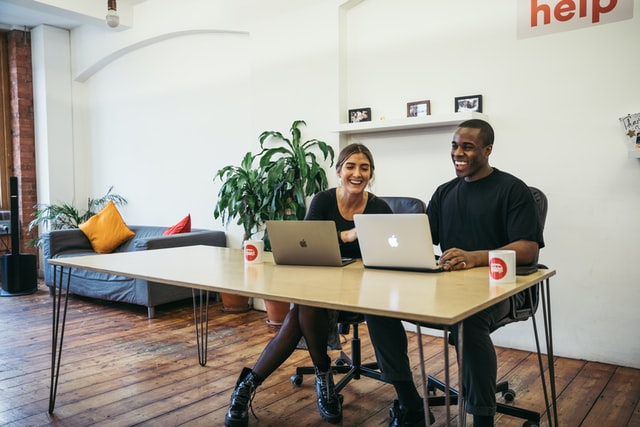 A man and woman laugh as they work together on two laptop computers.