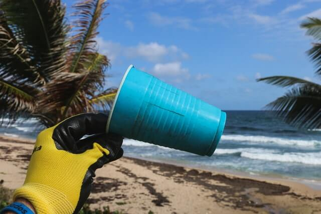 A gloved hand holds up a plastic yellow cup on the beach.