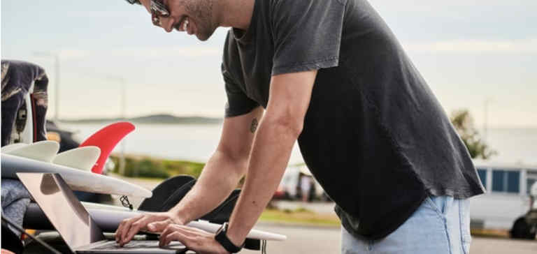 A man in a grey shirt works on a laptop computer outside.