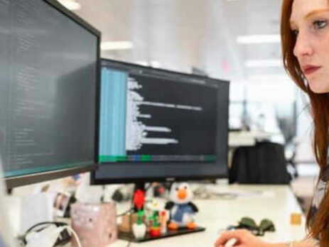 A redhead woman works on a computer with multiple monitors.