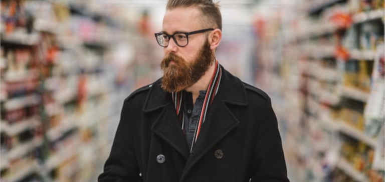 A bearded man shopping in a supermarket.