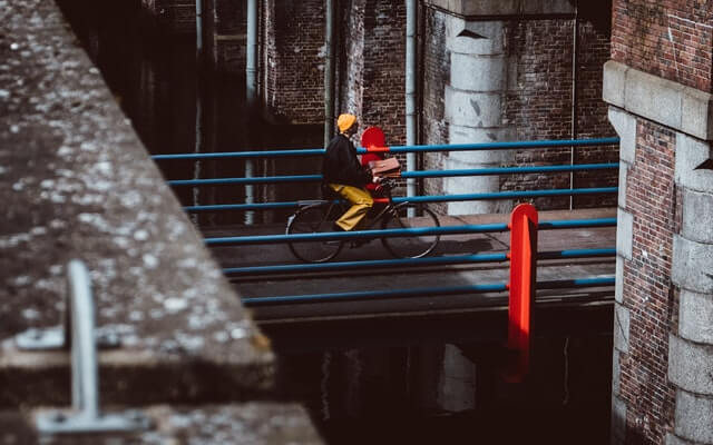 A man in a yellow hat rides a bicycle over a bridge.