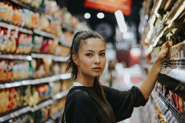 A woman takes something off a shelf at a grocery store.