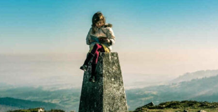 A girl reads a book on top of a pedestal on a mountain.