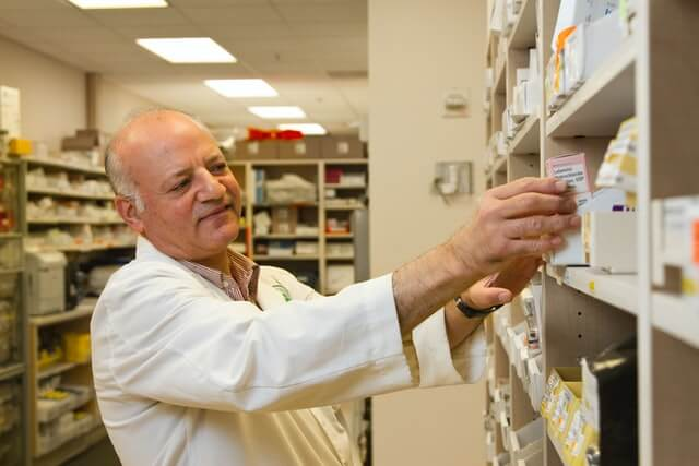 A pharmacist in a white coat examines medicine on a shelf.