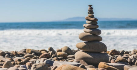 A tower of stones next to a beach on a sunny day.