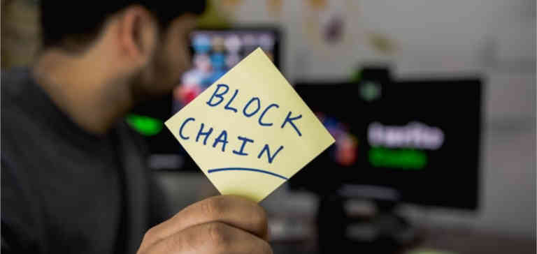 """Someone holds a sticky note that says """"blockchain"""" on it."""