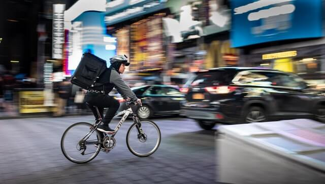 A person makes a delivery by bicycle.