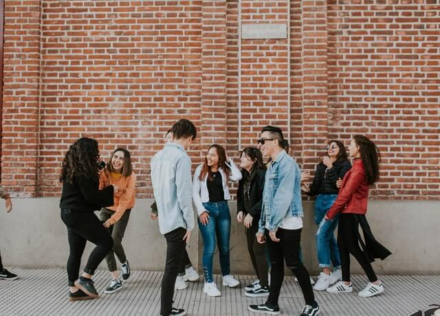 Many people stand near a brick wall laughing with one another.