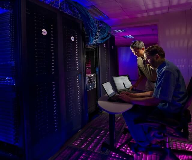 Two men work near a large data server.