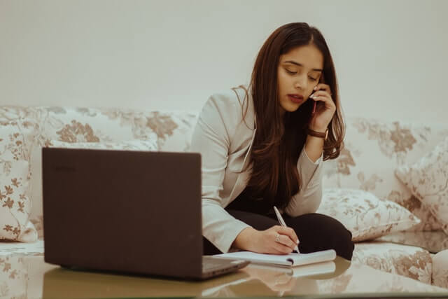 A woman in a white blazer writes and talks on the phone near a laptop.